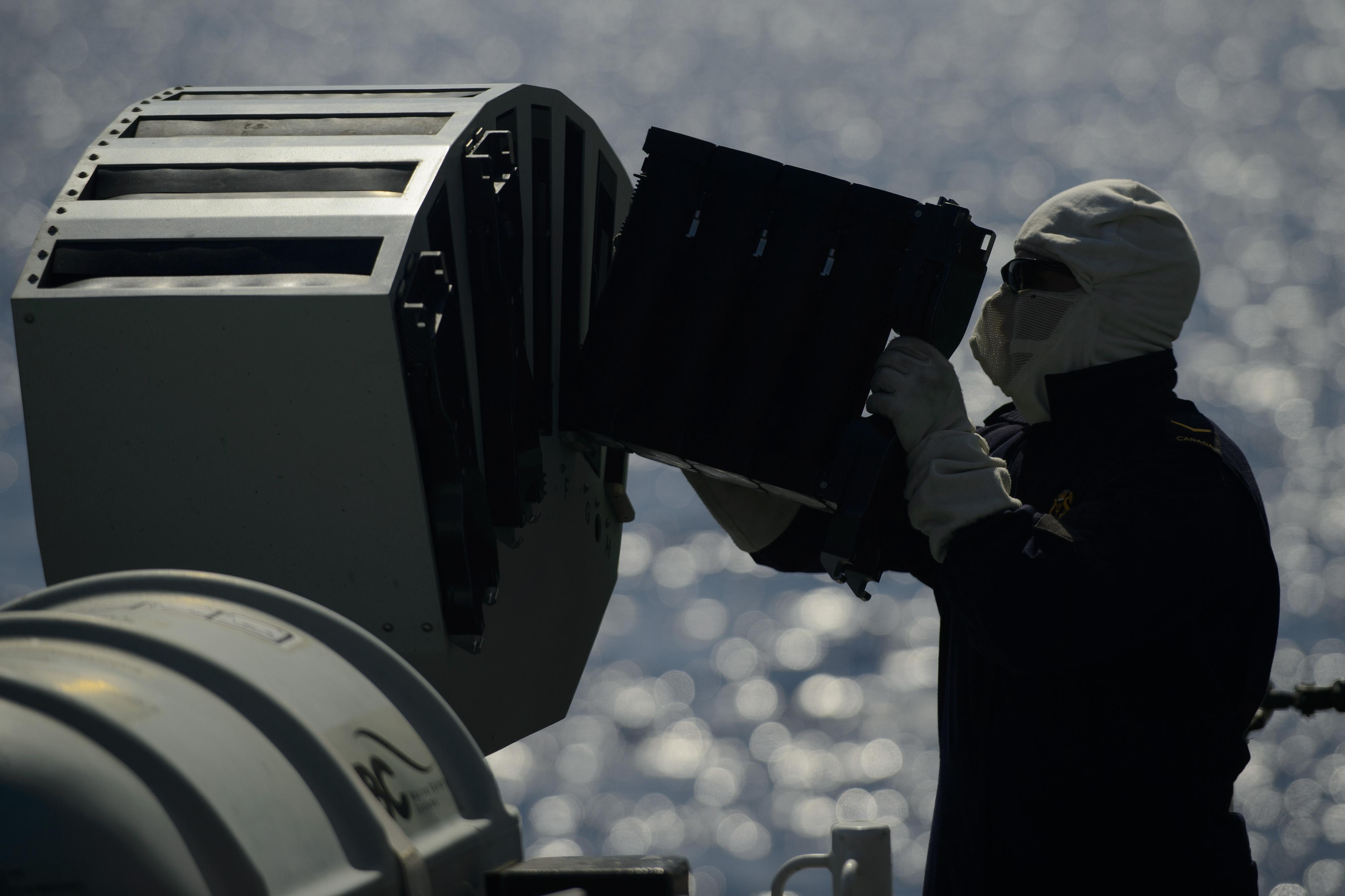 A Weapons Engineering Technician loads the ship's Multi Ammunition on Soft Kill System (MASS) aboard Her Majesty's Canadian Ship WINNIPEG during Operation REASSURANCE on July 20, 2015. Photo: Cpl Stuart MacNeil, HMCS WINNIPEG ET2015-5041-005 ~ Un technicien en génie des armes charge le Système de mise hors de combat de multi munitions (MASS) du navire à bord du Navire canadien de Sa Majesté WINNIPEG au cours de l'opération REASSURANCE, le 20 juillet 2015. Photo : Cpl Stuart MacNeil, NCSM WINNIPEG ET2015-5041-005